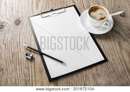 Clipboard with blank letterhead coffee cup pencil and sharpener on wooden background. Mock up for your design. Responsive design template.