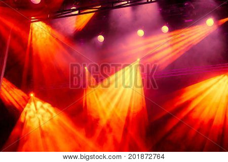 Yellow and red light rays from the spotlight through the smoke at the theater or concert hall. Lighting equipment for a performance or show.
