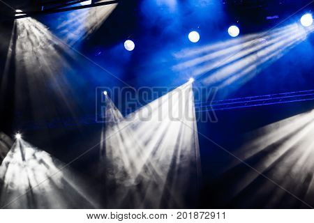 White and blue light rays from the spotlight through the smoke at the theater or concert hall. Lighting equipment for a performance or show.