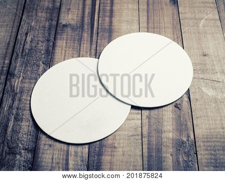 Two blank white beer coasters on vintage wooden table background.