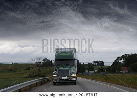 large lorry, truck driving at night in stormy dark weather
