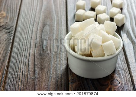 White sugar in bowl on wooden background. Selective focus horizontal. A few sugar cubes are near the full glass with white sugar. Intake of bad calories.