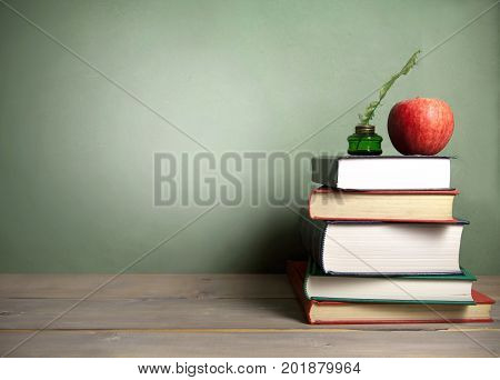 Stack of books with apple and quill next to a chalkboard background