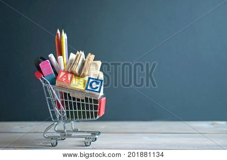 Shopping cart filled with stationery merchandise against chalkboard