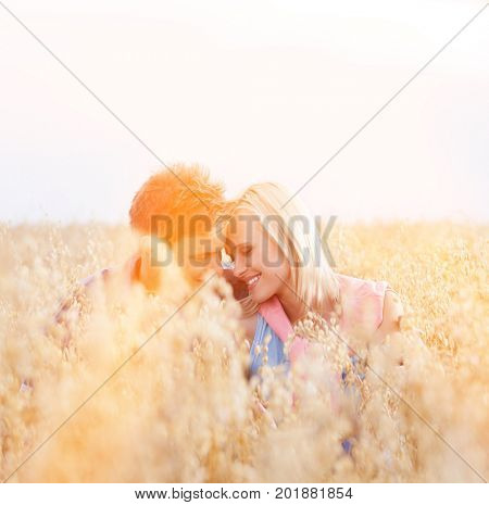 Romantic young couple sitting amidst field