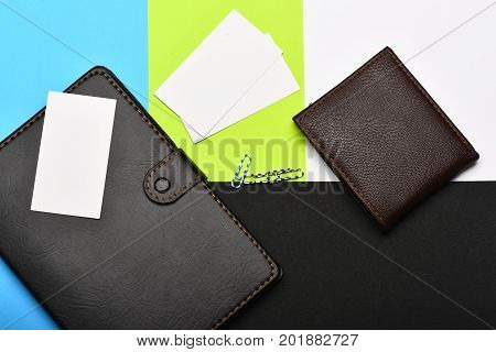 Leather wallet and stationery. Business and work concept. Notebook blank business cards and paper clips. Office tools isolated on colourful background top view.
