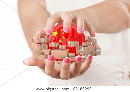 Two Woman Hands Protecting Sphere with China Flag Surrounded by Cardboard Boxes with Parcel Goods on a white background.