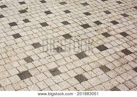 Cobbles of white and black squares, An old road paved with stone. Beautiful unusual background.