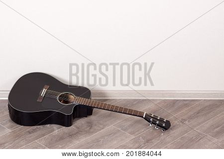 Black Classical Acoustic Guitar in an Empty Room lying on floor in front of the Wall with Copy Space extreme closeup