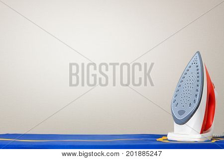 Iron on Ironing Board Against a White Wall with Copy Space extreme closeup