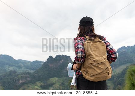 Rear view of female hiker looking at map in forestHiker woman look binoculars on the mountain background blue sky Thailand select and soft focus