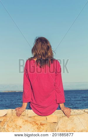Lonesome girl sitting on the coast and watching the sea / ocean.