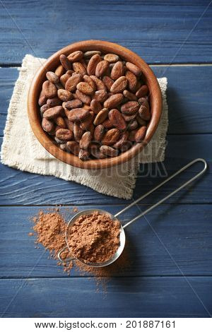 Cocoa beans in bowl and sieve with powder on wooden background