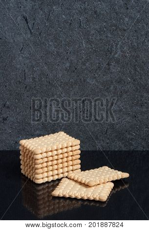 A vertical stack of square biscuit crackers are laid on a black background with a reflection with copy space