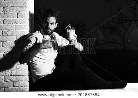 young handsome bearded sexy macho man with stylish beard in white shirt sitting on windowsill and holding glass of nonalcoholic cocktail on black and brick wall background copy space