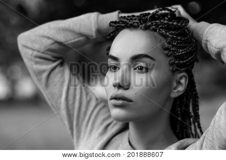 A black-and-white portrait of a beautiful girl with perfect cheekbones. er hair is plaited in pigtails in braids.