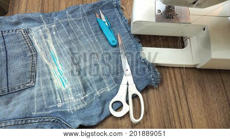 Sewing repairing the Jeans shorts by machine home made size has lighting lamp and accessories.