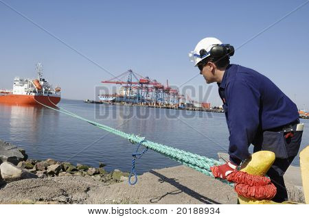 dock-worker securing ship with hooks and lines outside container port