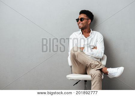 Smiling happy african man posing in a chair and looking away while holding mobile phone isolated over gray background