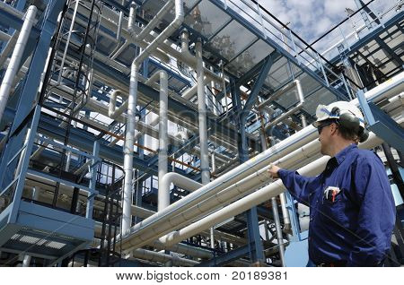 engineer pointing at pipelines and pumps inside large oil refinery