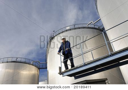engineer overlooking oil-storage-tanks, sunlight reflecting in tanks