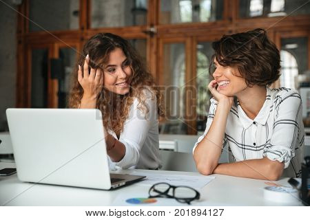 Two pretty happy women working by the laptop computer in co working office