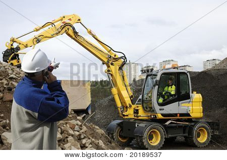 engineer supervising digger, bulldozer and driver