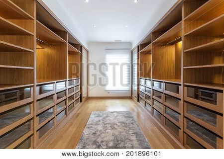 Large wardrobe room, with empty shelves. In house