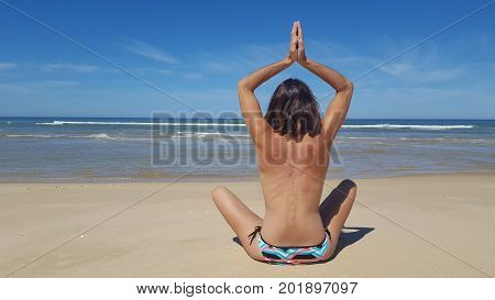 Young Healthy Topless Woman Practicing Yoga On The Beach