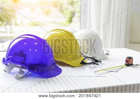 The safety helmet and the blueprint on table at construction siteSafety helmet whiteblue and yellow for foreman/engineer/architect/visitor use in construction site for safety workworkerindustry