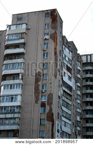 Cracks and stains on the walls of the high-rise building. Dampness.