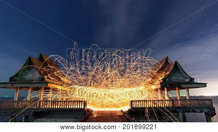 Burning steel wool fireworksLine of light in circle from fire swing dancing Art shown at night time
