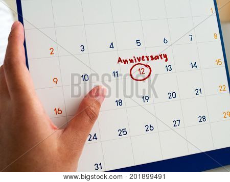 Woman hand hold white calendar written red circle and Anniversary word marked on white calendar. This Anniversary marker to remind you an important appointment.
