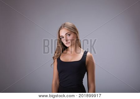 Young woman girl in black dress studio portrait. Blonde hair model female in black short dress over gray background
