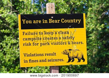 A Bullet Riddled Yellow You Are In Bear Country Warning Sign