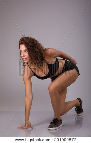 Healthy young woman preparing for a run. Fit female athlete ready for a spring over grey background with copy space. Low start position over gray background
