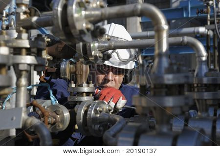 engineer standing behind pipeline machinery inside oil refinery