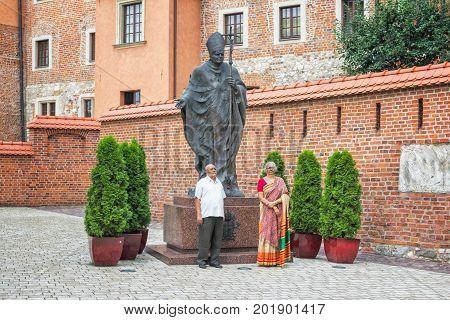 Krakow/Poland- August 14, 2017: Wawel Royal Castle, tourists - senior Indian couple, wearing traditional clothes, taking photo near monument of Pope Saint John Paul II