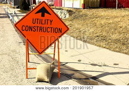Temporary Utility Construction Ahead Sign Beside A Sidewalk
