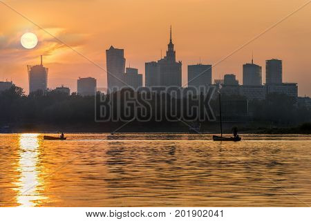 View of the Warsaw city center from the Vistula river at sunset.