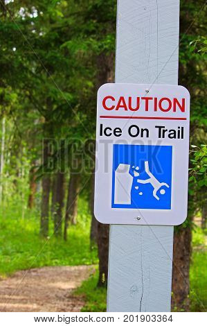 A caution ice on trail sign in summer