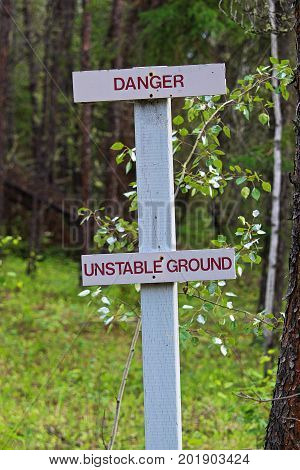 A Danger, Unstable Ground Sign Along A Hiking Trail
