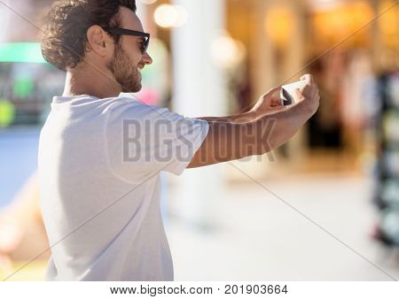 Digital composite of Man taking casual selfie photo in front of Shopping Mall
