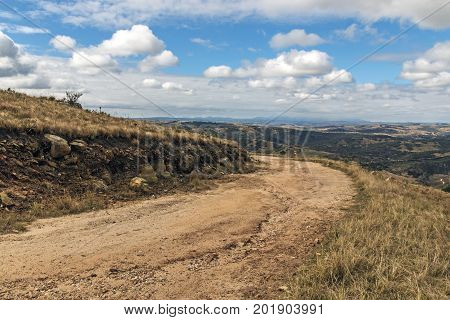 Curved Dirt Road Through Dry Grass Against Winter Landscape