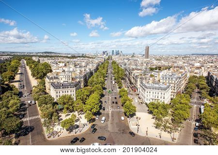 Aerial wide angle cityscape view on the beautiful buildings and avenues near the Triumphal arch with skyscrapers on the horizon in Paris
