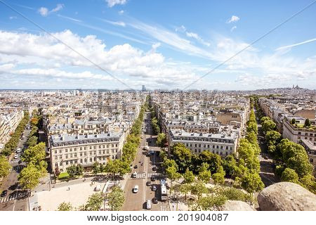 Aerial wide angle cityscape view on the beautiful buildings and avenues near the Triumphal arch with Monmartre hill on the background in Paris