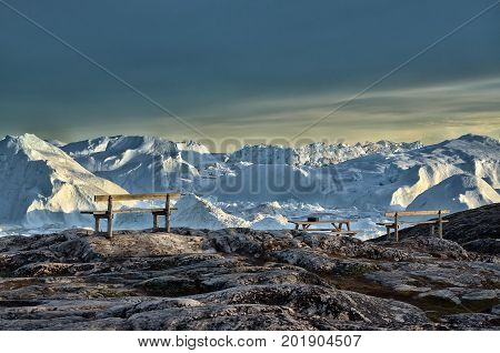 View of the Sermeq Kujalleq glacier in the midnight sun with  table and bench, Disco bay, Ilulissat,Jakobshavn, Greenland.