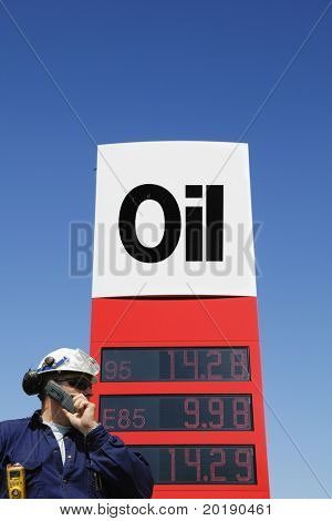 oil-worker, engineer in hard-hat, standing in front of large oil and fuel sign, grades of oil and fuel