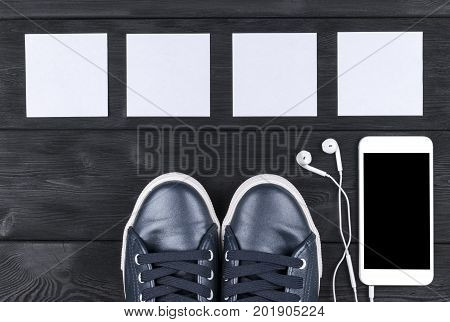 Overhead view of sports shoes by mobile phone with isolated screen and in-ear headphones and white empty blank sheets on black wooden table floor. Empty space for text copy space empty blank screen