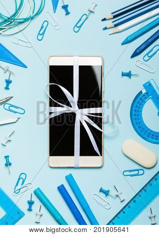School supplies of blue and white colors on a blue background and new phone as a gift. Male or boyish present and the topic of school study office work. Flat lay
